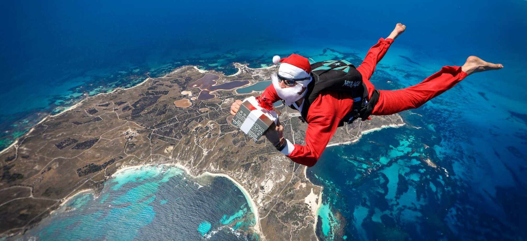 Santa with a present skydiving over rottnest